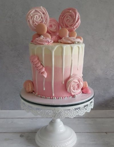 Pink and white drip birthday cake with macarons and meringues