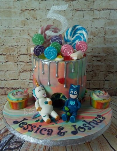 Children's unicorn and Catboy birthday cake with sweet decorations and cupcakes