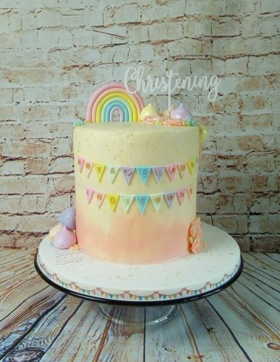 Christening cake decorated with buttercream and edible bunting and a pastel rainbow